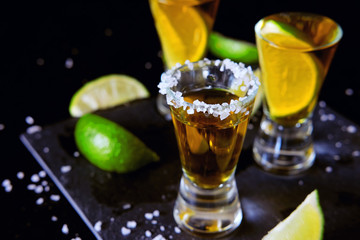 Strong alcohol drinks. Tequila shots with salt and lime slices.