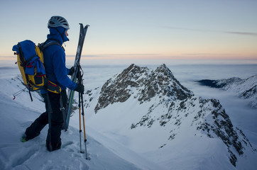 skier on top of the mountain admiring the sunset