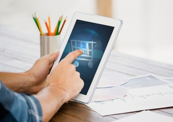 Man touching shopping cart icon on digital tablet