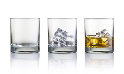 Empty glass, glass with ice cubes and glass with whiskey and ice cubes. Isolated on white background