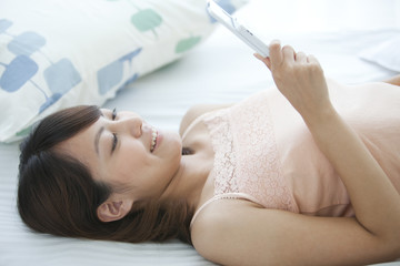 Young Woman Using Mobile Phone in Bed
