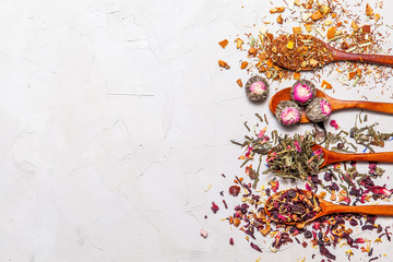 Dry tea in wooden spoons on grey background, top view. Leaves of red, fruit , green and black tea with  fruits and spices