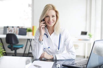 Female doctor. Shot of a middle aged female doctor talking with her patient on mobile phone while sitting in front of laptop.