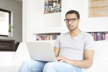 Browsing on the internet. full length shot of a smiling young afro American man using a laptop while relaxing in his living room at home.