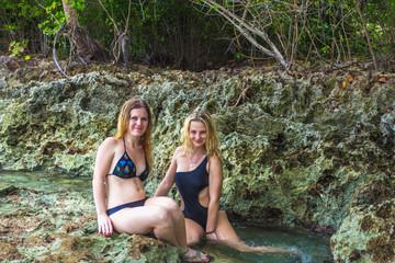 Two girls models in bikini sitting on the rocks near wild shore. Samana, Dominican Republic