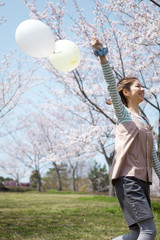 Young woman running with balloon
