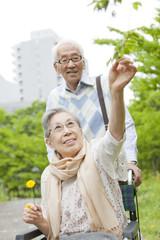 Senior man pushing senior woman on wheelchair, Kanagawa Prefecture, Honshu, Japan