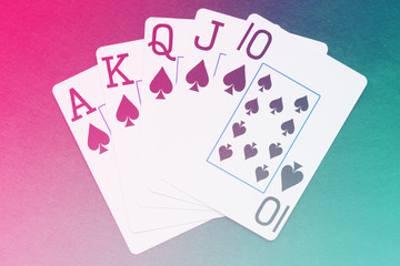 Royal Flush playing cards hand on colorful background