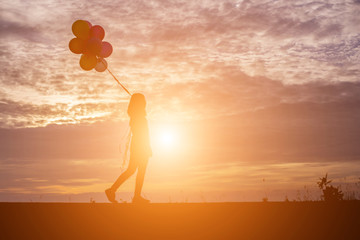 silhouette of young woman holding colorful of balloons with sunset