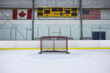 A wide angle view of a hockey net on a recreational hockey rink. A blank scoreboard, Canadian and American flags hang on the wall overhead.