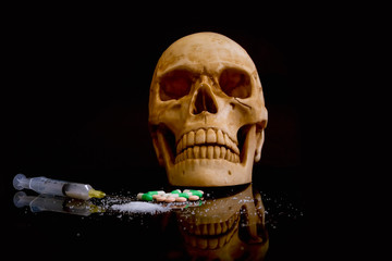 Still life human skull with concept Drug make you death,with a pill cocaine in plastic packet  hypodermic syringe in black background