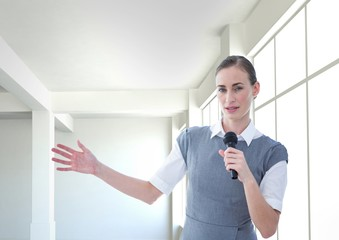 Businesswoman public speaking on microphone in office