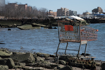 Scrap of shopping cart in a cemetery of boats in Coney Island, New York City