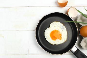 Keuken foto achterwand Gebakken Eieren fried egg heart-shaped for breakfast on plate