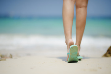 thongs slipper in legs of woman walking on the sand of beach at seaside in background