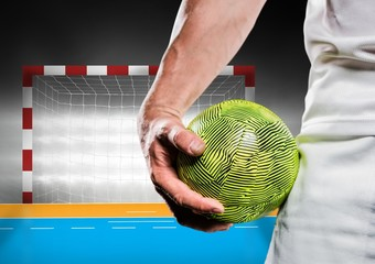 Close-up of male handball player holding ball against goal post