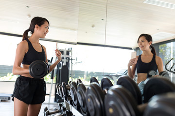 Woman exercising with weights and taking selfie in gym
