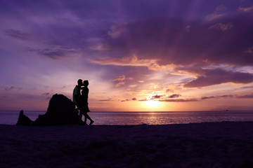 Silhouette couple kissing on the beach purple sky sunrise background