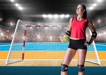 Female athlete holding handball against stadium in background