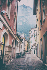 Wąska ulica na tle gór. Riva del Garda, Włochy - 140870219