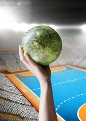 Hand of athlete holding ball against stadium background