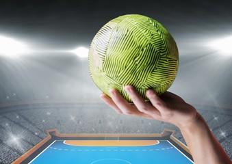 Hand of athlete holding ball against stadium background