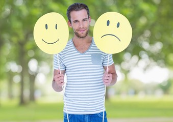 Conceptual image of man holding happy and sad smiley faces