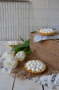 Tartlets with merengue on a stand with lemon jam, still life. romantic morning