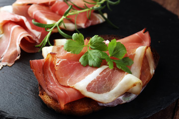 Bread with slices jamon serrano for lunch table. Sharing antipasti on party or summer picnic time over wooden rustic background.
