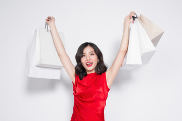 Cheerful fashionable asian woman wearing a red dress with shopping bags standing over white.