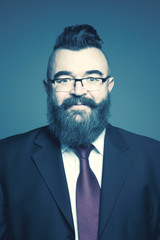 Adult bearded man in a suit, glasses and a mohawk hairstyle on a blue background. Toned