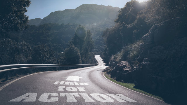 long deserted road through mountains with concept words time for action and arrow on asphalt