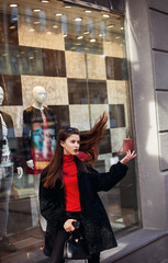 The concept of street fashion. portrait of Young girl dressed in a fashionable outfit. Posing against the window of the boutique