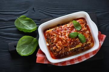 Lasagna bolognese over black wooden background, top view, studio shot