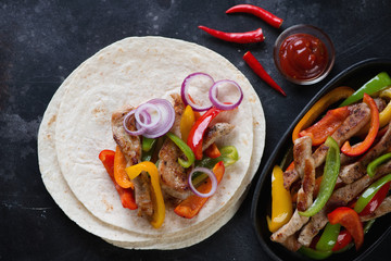 Above view of wheat wraps with tex-mex pork fajitas on a dark stone background