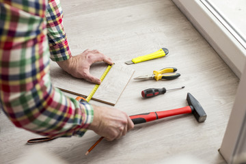 Worker puts laminate. In the picture a man's hands and different instruments