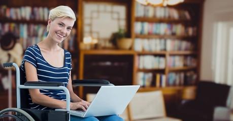 Portrait of woman sitting on wheelchair using laptop