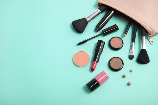 Make up products spilling out of a pastel pink cosmetics bag on to a turquoise background, with blank space at side