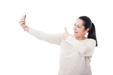 Pretty female posing joyfully at her smartphone