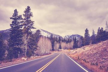 Vintage toned Rocky Mountains asphalt road in autumn, Colorado, USA.