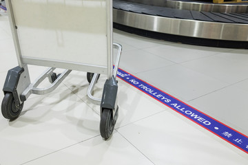 """Sign of """"No trolley beyond this line"""" in the airport, luggage drop area"""