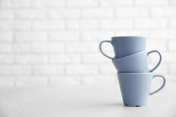 Grey cups on table against white brick wall background