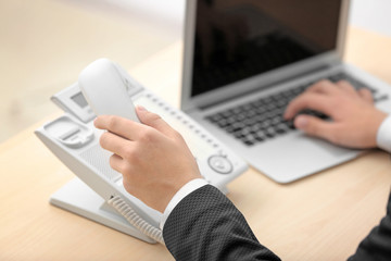 Hand of man picking up telephone receiver in office