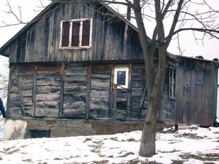 old wooden hut in village winter landscape