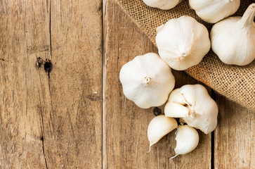 peeled white garlic in gunny sack cloth on brown wooden table with copy space, top view