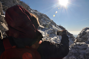 Mountaineer take selfie on top of a mountain in the sun