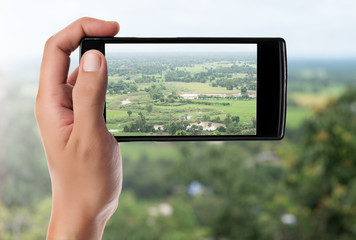 hand taking picture at the mountain landscape with a smart phone
