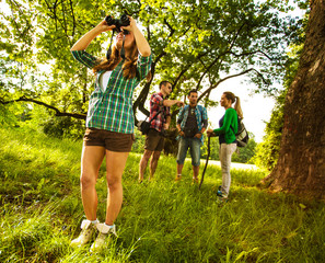 Day in nature.One female  using binoculars. Her friends are in background standing and talking.
