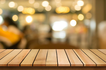 Wood table top on blur bokeh restaurant background can be used for display or montage your products