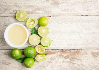 freshly squeezed lime juice with lime fruits on wood table,top view